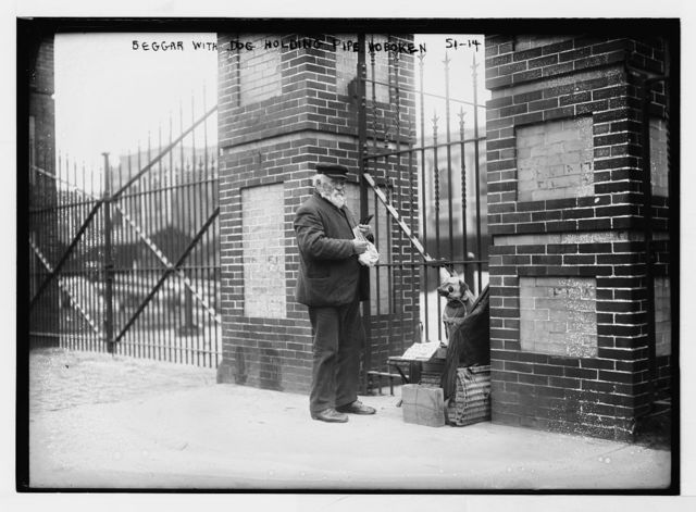 Beggar, holding pipe, with dog, Hoboken, N.J.
