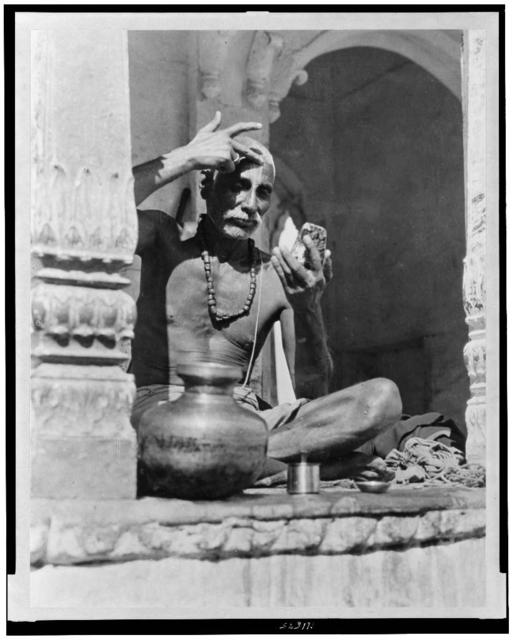 [Brahman priest, in India, painting his forehead with the red and white marks of his sect and caste]
