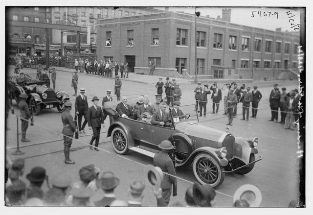 [Car driving through procession]