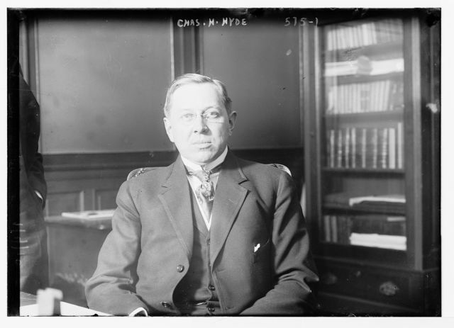 Chas. H. Hyde, seated in study