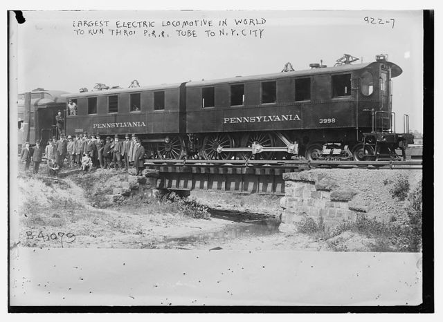Crowd standing in front of Penn. R.R. car -- the largest electric locomotive in the world, to run through Penn. R.R. tube to N.Y. City