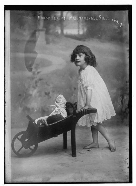 Daughter of Mrs. Marshall Field, pushing doll cart