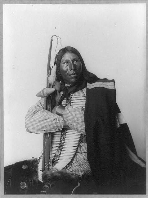 [Distributor, Native American man, three-quarter length portrait, seated, facing right; arms folded, holding bow, arrow, and tomahawk; dressed in bone breast plate]