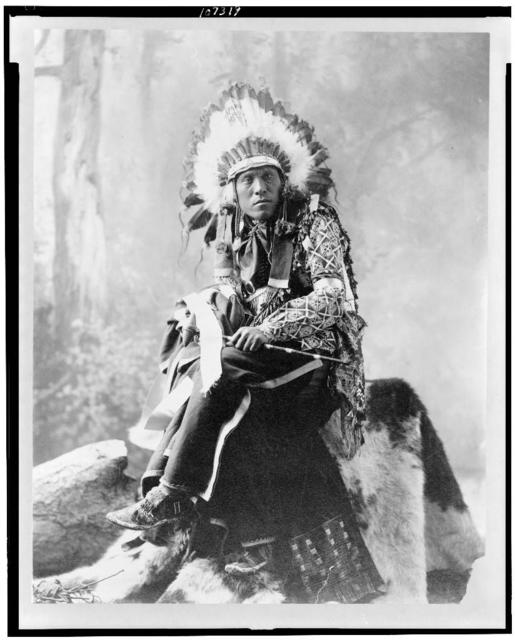 [Eagle Bear, full-length portrait, seated, facing front]