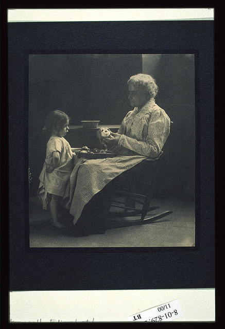 [Elderly woman in a rocking chair peeling apple with young girl standing in front of her]