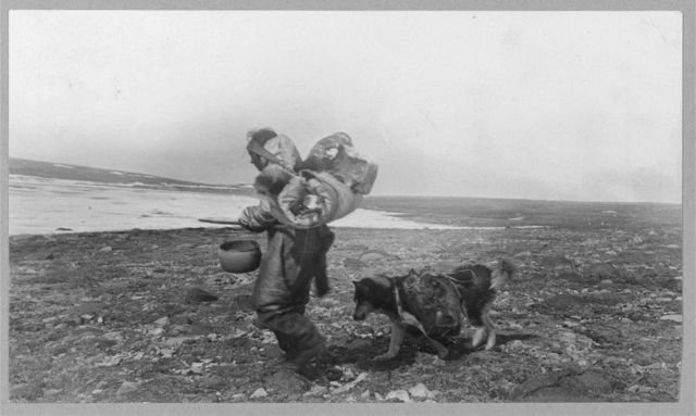 Eskimo woman and dog traveling in summer