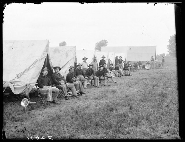 First regiment band of the Nebraska National Guard pictured sitting outside their tents, Kearney, Nebraska.