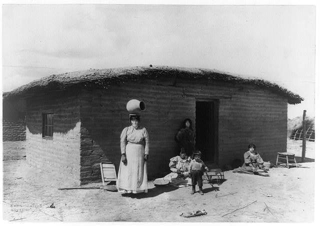 [Five Pima Indians posed outside adobe house--one woman is standing with a piece of pottery on her head]