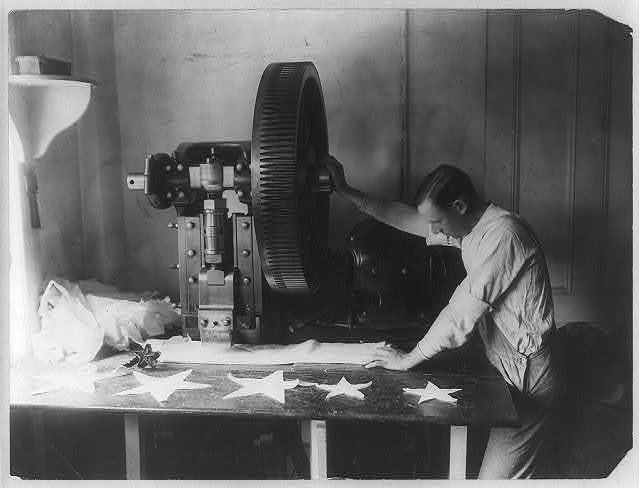 [Flag making - man cutting out stars with machine]