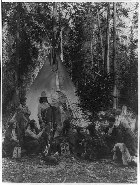 Flathead Indians holding pre-Christmas family gatherings on the west side of Glacier National Park, in the dense forest of evergreen trees that skirt the Rocky Mountains