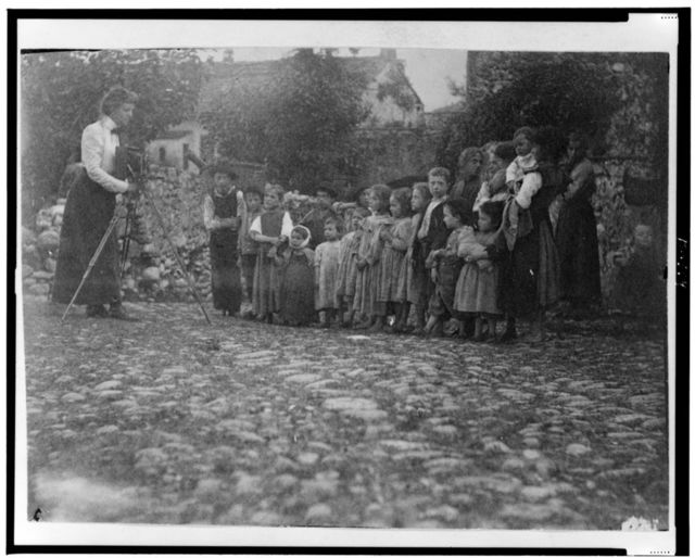 [Frances Benjamin Johnston photographing a group of people, mostly children, in Europe]