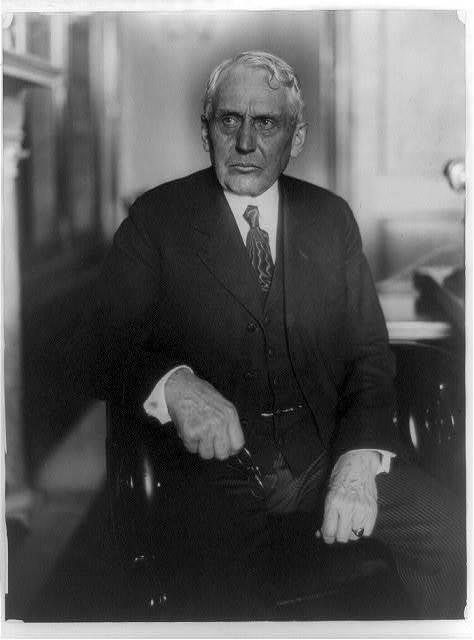 [Frank Billings Kellogg, three-quarter length portrait, seated, facing left, holding eyeglasses]