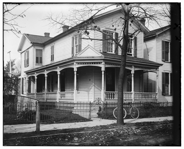 [Front view of 7 Hawthorn Street, the Wright home, with bare trees and a bicycle resting by the right gate of the front fence, about 1900]