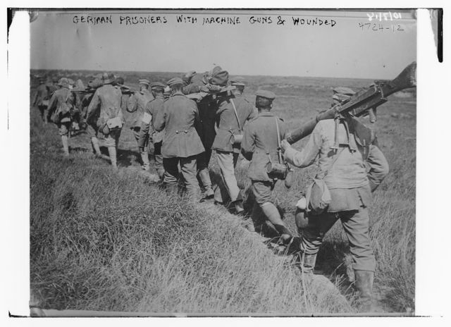 German prisoners with machine guns & wounded