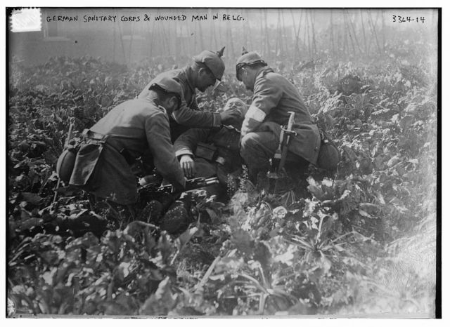 German Sanitary Corps & wounded man in Belg. [i.e., Belgium]
