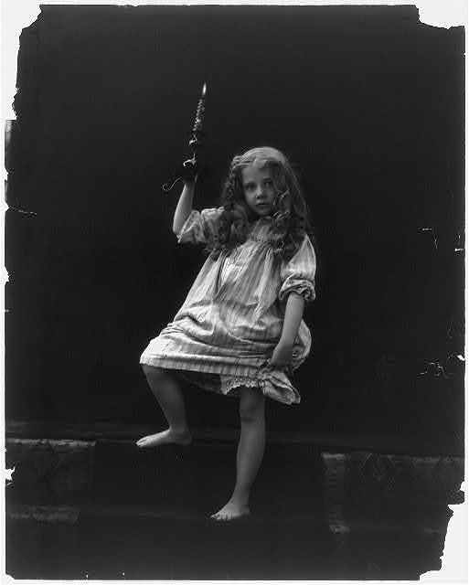 [Girl in nightgown holding candle on steps]
