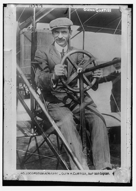Glenn Curtiss at pilot's wheel of his biplane
