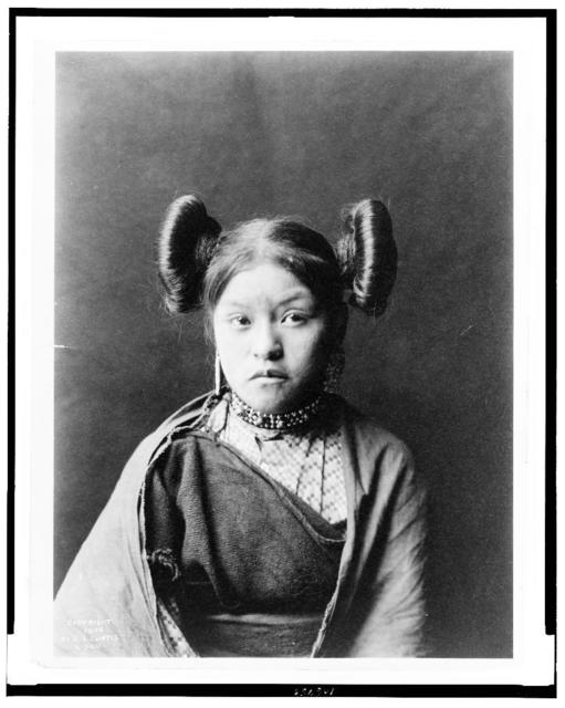[Gobuguoy, Walpi girl, half-length portrait, facing front, hair tied in swirls on sides of head, metal bead and bell choker, printed cotton dress, cotton shawl around shoulders]