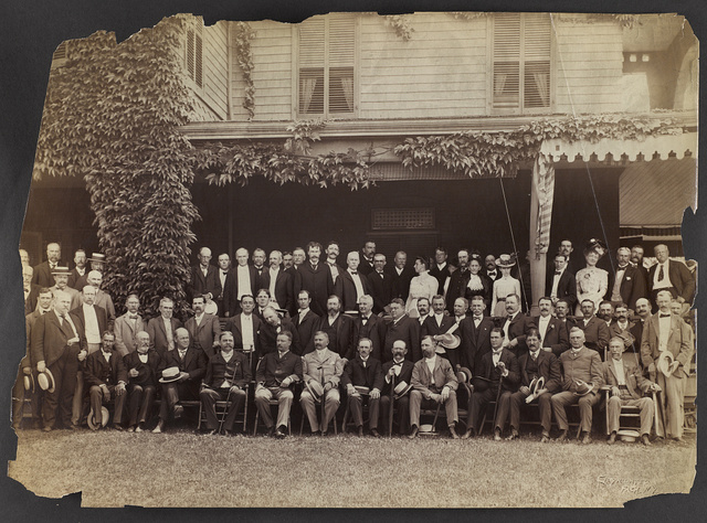 [Group portrait of Theodore Roosevelt, seated in front row, left center, with group of men and women]