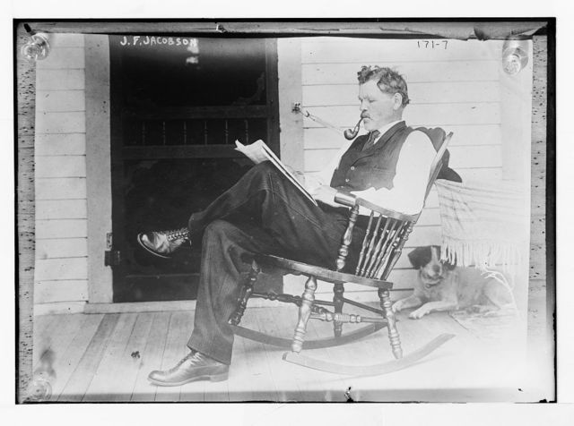 J.F. Jacobson, reading, in rocker, with dog