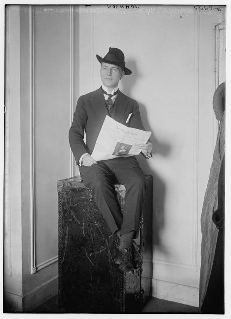 Johnson [seated on a trunk, reading newspaper]
