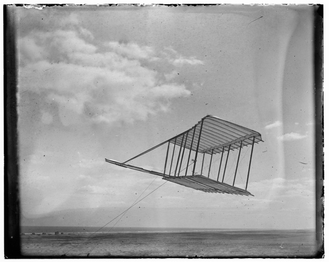 [Left side view of the 1900 Wright glider before installation of forward horizontal control surface, flying as a kite, tipped forward; Kitty Hawk Lifesaving Station and Weather Bureau buildings in background to the left]