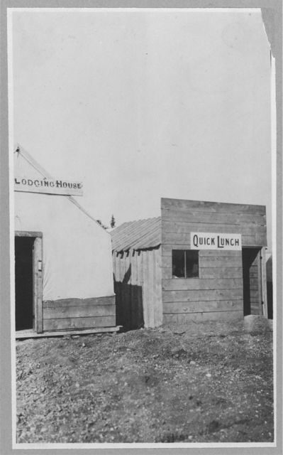 "[""Lodging House"" and ""Quick Lunch"" shacks on a dirt road]"