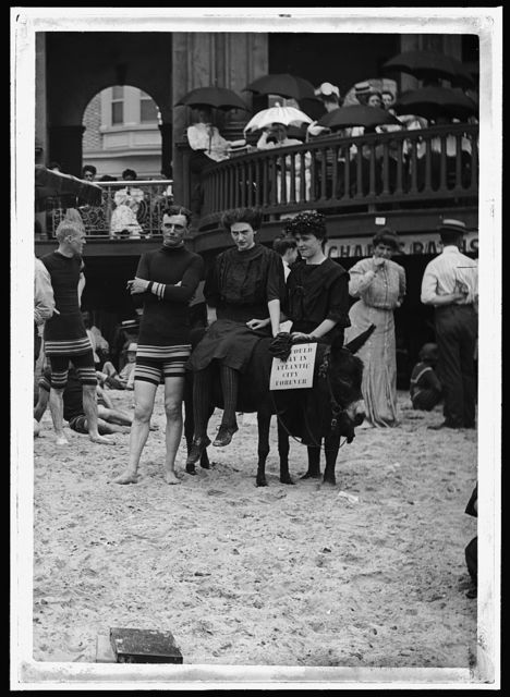 [Man and women posed on donkey for photo at crowded beach, Atlantic City, N.J.]