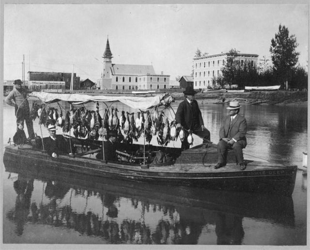 Marshall Erwin in front of a boat containing a kill of ducks