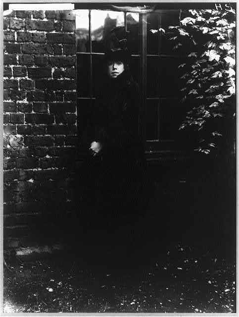 [Maud Franklin, full-length portrait, wearing fur-trimmed(?) coat and hat while posed standing outdoors in front of a window]]