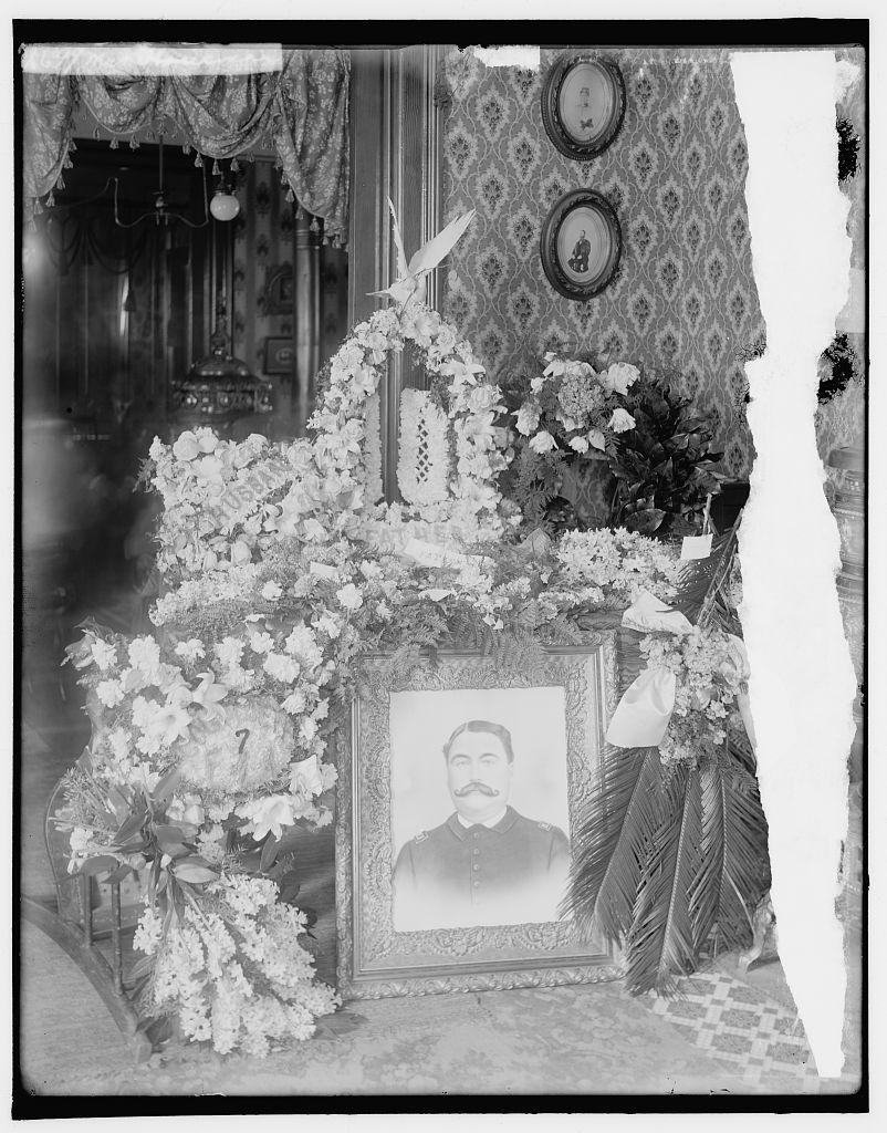 [Memorial corner with wreaths surrounding portrait of man]