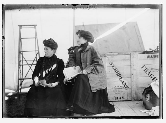 Miss Sperder, seated with another lady, holding newspaper