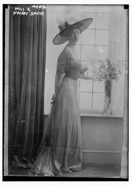 Miss V. Mackay Smith standing next to vase of flowers