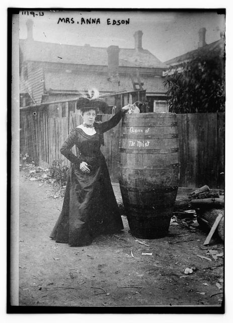 """Mrs. Anna Edson standing next to huge barrel upon which is written """"Queen of the Mist"""" and upon which is sitting a cat"""