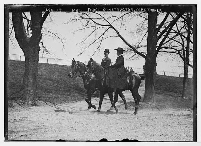 Mrs. Fisher and Capt. Turner, her instructor, horseback riding in park