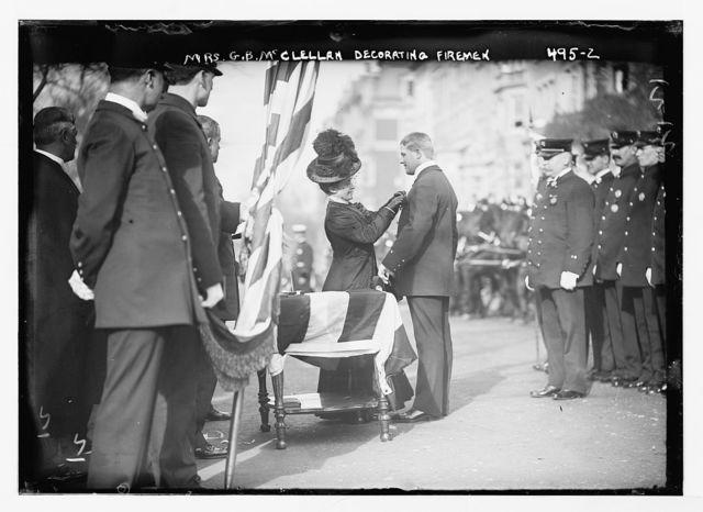 Mrs. McClellan, wife of Mayor, decorating honor men of N.Y. Fire Dept., New York