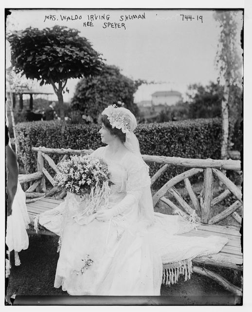 Mrs. Waldo Irving Shuman, nee Speyer, seated on bench, holding bouquet of flowers