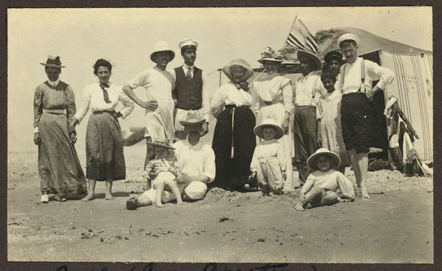 [Mrs. Weston, standing in center, and friends at the beach in Jaffa with an American flag waving in background]