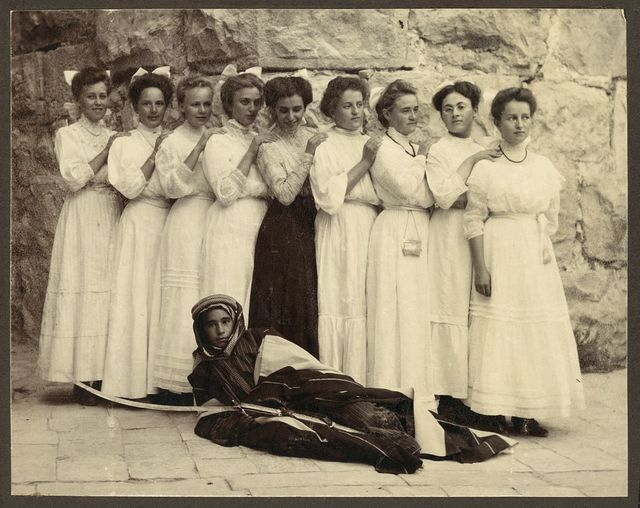 [Nine girls standing over young boy holding sword and dressed in traditional Bedouin clothing]