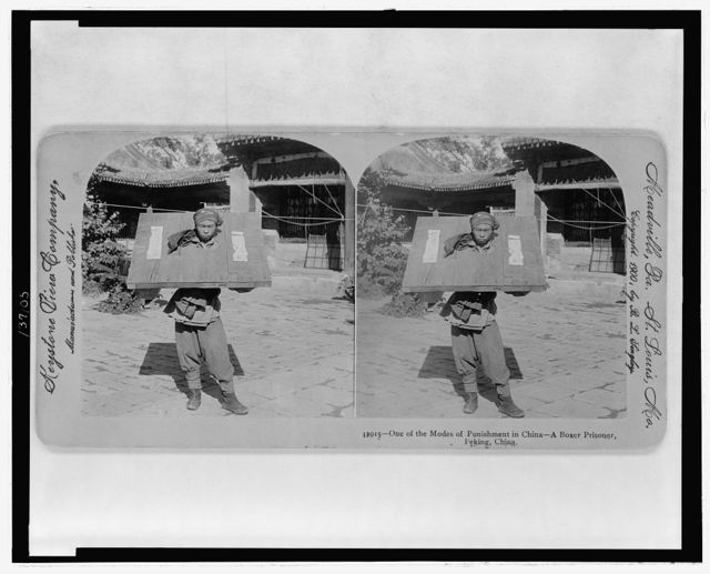 One of the modes of punishment in China - a Boxer prisoner, Peking, China