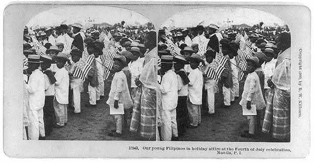Our young Filipinos in holiday attire at the Fourth of July celebration, Manila, P.I. [holding U.S. flags]