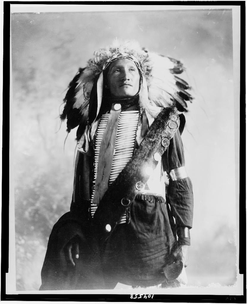 [Plenty Holes, a Sioux Indian in feather headress and bone breastpiece, half-length portrait, standing, facing slightly right]