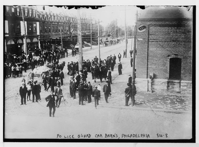 Police guard car barns, crowd stands nearby, Philadelphia