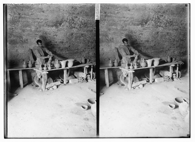 [Potter working on wheel, pottery on table in front of him]