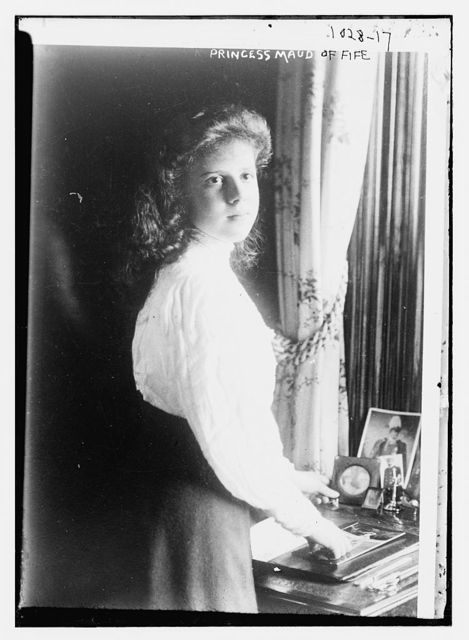 Princess Maud of Fife, standing at table upon which there are photos