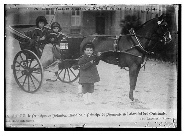 Princesses Yolanda and Mafalda in horse-drawn carriage, beside which stands the Crown Prince of Italy