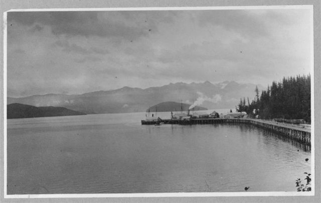 [Railroad trestle with loading dock jutting into bay; snow-capped mountains in background]
