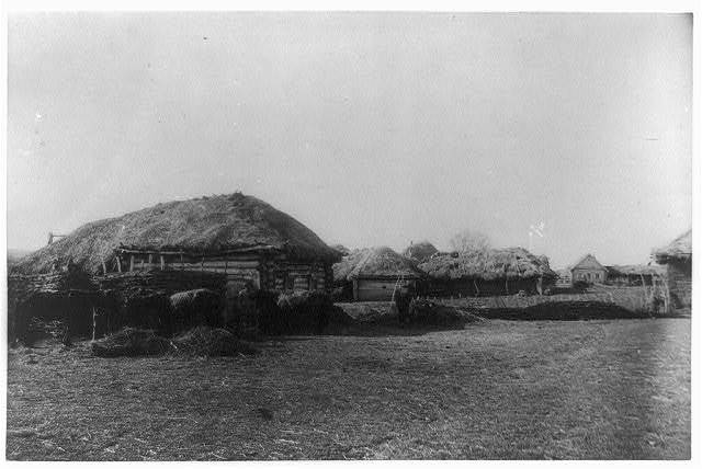 [Russian farm scene showing thatched-roof buildings, with horses and barn in left foreground]