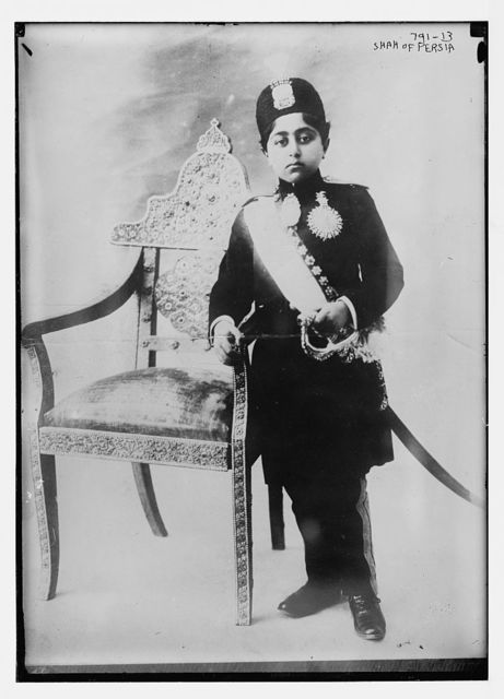 Shah of Persia, in uniform, standing by chair