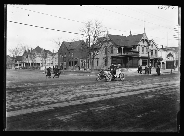 [Street with automobile and Moesta's store]